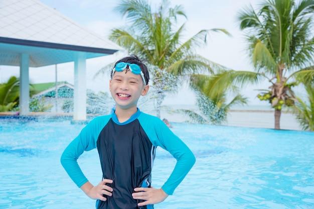 屋外のスイミングプールで泳いで笑顔で若いアジアの男の子