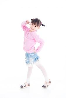 立っている小さなアジアの女の子と白い背景の上の笑顔