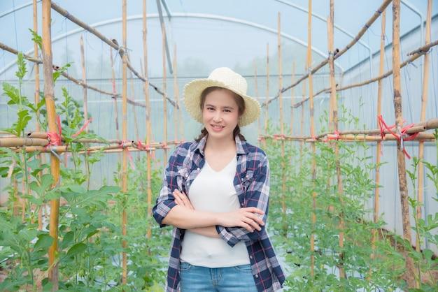 Красивый азиатский фермер стоя с пересеченной рукой и улыбками в ее ферме дыни.