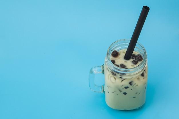 青い背景にガラスの瓶に泡ボバとアイスミルクティー