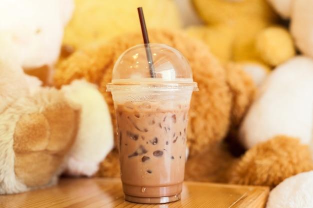 ココアはストローでカップに氷で冷やしてカフェでクマ人形でそれを木のテーブルに置く