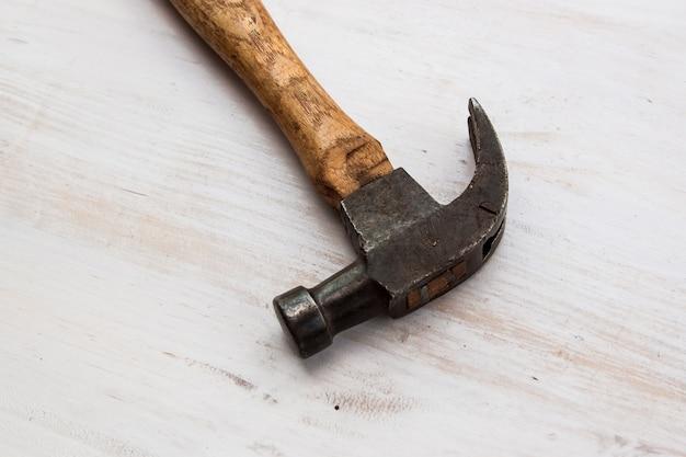 Старинный молоток на краске белого цвета, деревянный пол, деревянная ручка и стальной молоток