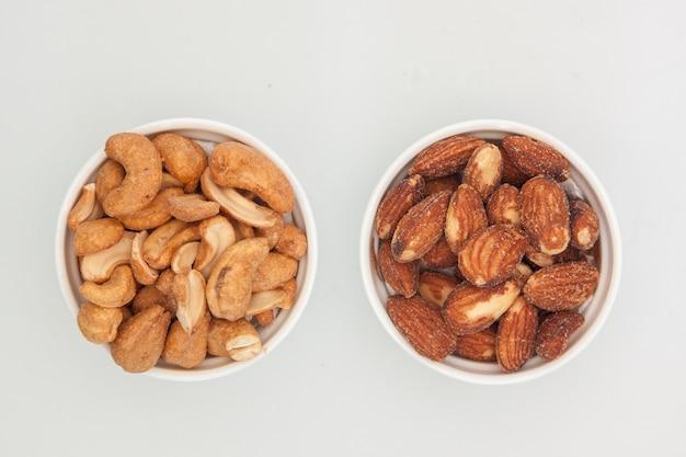 Миндаль орехи и кешью в белой чашке на белом фоне