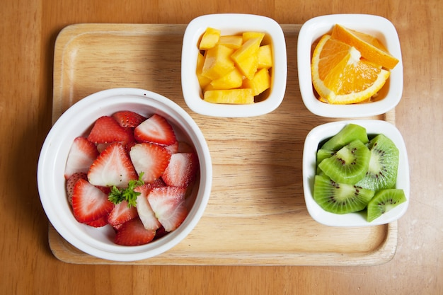 木製トレイ、イチゴ、マンゴー、キウイとオレンジのミニカップのフルーツ