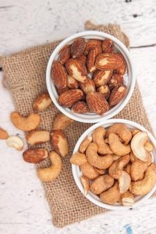 Миндаль и орех кешью в белой чашке и положить на мешковину на деревянный пол