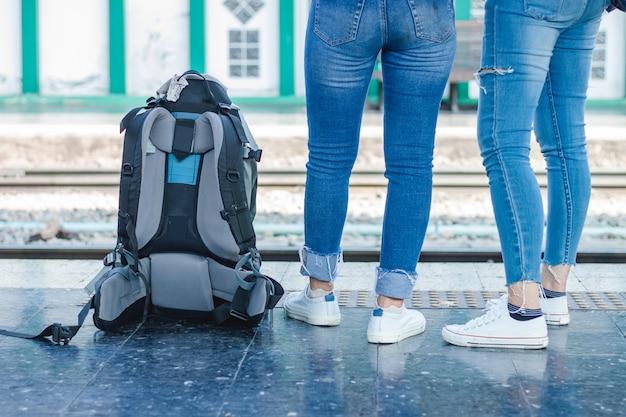 Два молодых путешественника женщина ждет поезд на вокзале для путешествий