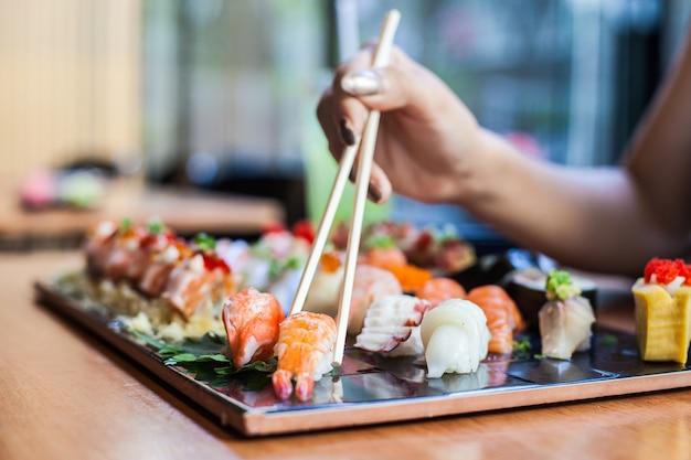 Суши, установленные на черной тарелке японская еда в ресторане с палочкой для еды