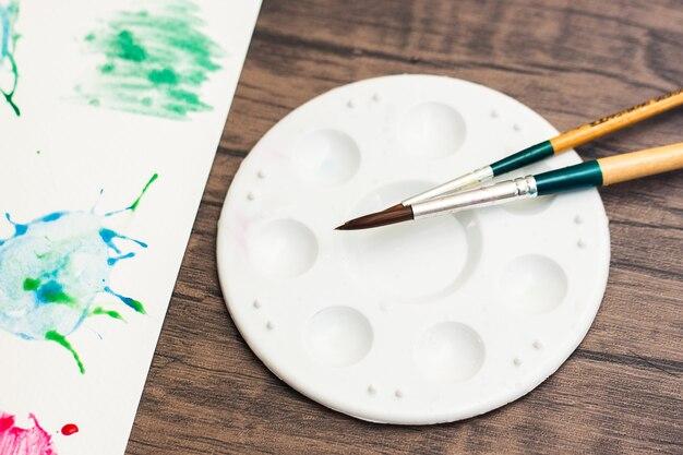 ディスクプレート混合水彩ペイントパレットと着色用のブラシは、紙に水彩画を描くために働きます。アートを作成するには