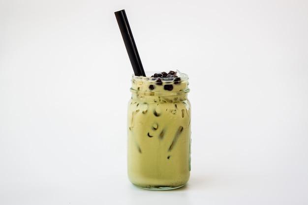 白い背景の上のガラスの瓶に台湾アイスミルクグリーンティー