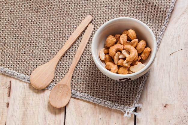 Закуски кешью в керамической миске с деревянными ложками