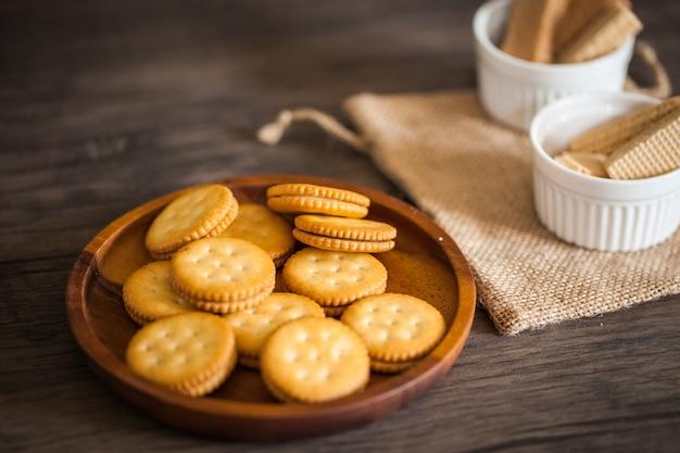 Крекеры и вафельное печенье для десертов для перекуса и кофе, положенные на деревянную тарелку и деревянный стол