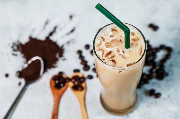 豆と粉のコーヒーと一緒に石のテーブルに置かれたアイスラテの新鮮なコーヒー。良い味の良い原料と新鮮な飲み物。
