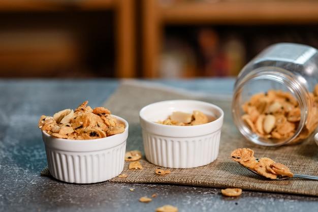 白いボウルにコーンフレークと穀物を入れて、毎日の新鮮な食事と健康的な食事のために、乳製品でおいしい朝食を食べましょう。