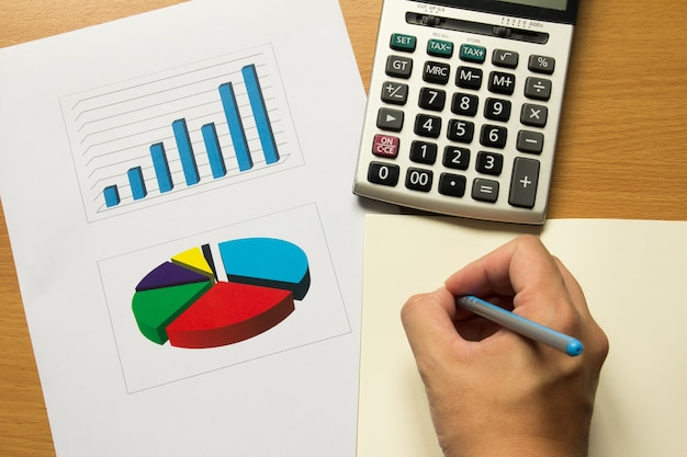Деловой человек написать записку с ручкой на финансовую диаграмму и график, калькулятор