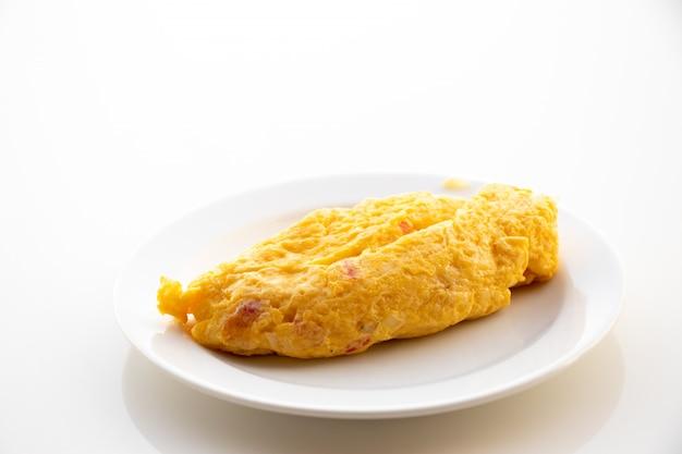 白いテーブル背景に皿の場所で卵のオムレツ