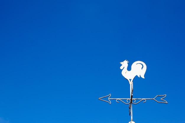 Белая петух флюгер показывает направление ветра на фоне голубого неба