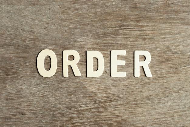 ウッドフラットに単語「順序」の木製文字を置く
