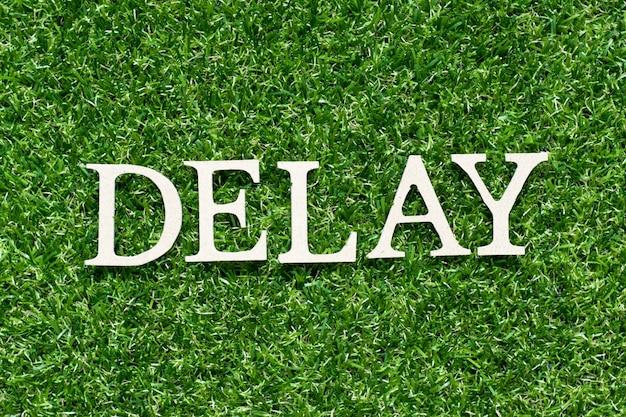 人工の緑の草に単語「遅延」の木製文字