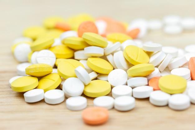 カラフルな薬錠剤錠剤や木製のテーブル背景に薬のクローズアップ