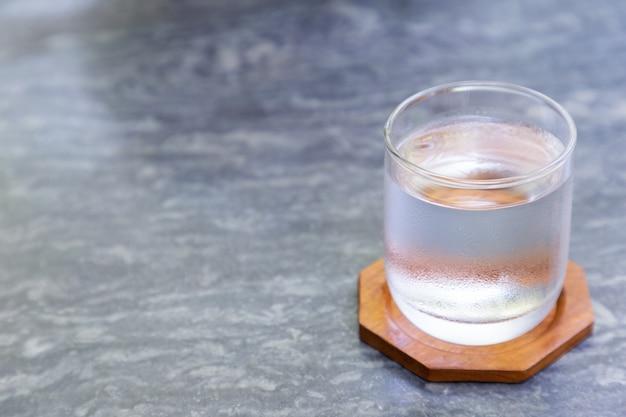 コーヒーショップで灰色の石のテーブルの上の木のコースターで冷たい水のガラス。