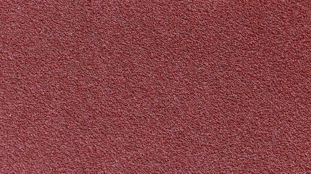 産業用建設のための赤い紙やすりテクスチャ背景