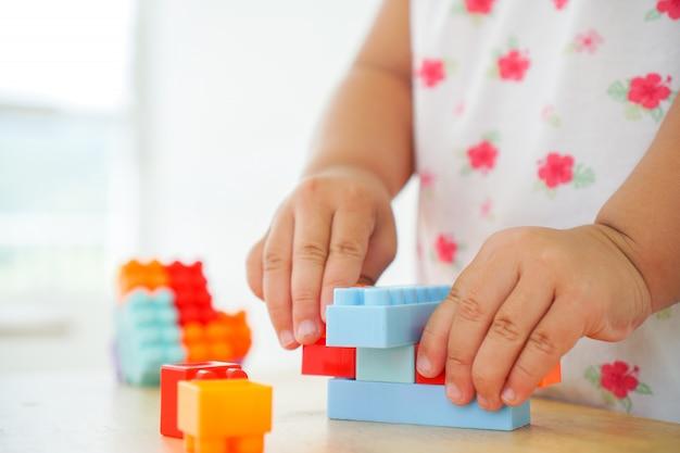 テーブルでカラフルなコネクタのおもちゃで遊ぶ子供の手のクローズアップ。就学前および幼稚園児向けの教育玩具。