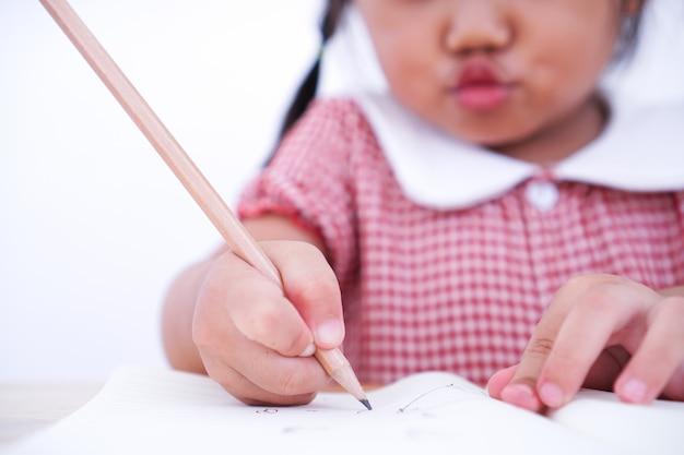 Закройте вверх по маленькому ребенку уча написать на бумаге.