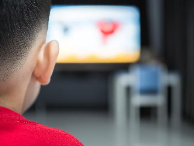 Мальчик смотрит телевизор, телевизионный эффект на детей