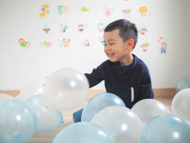 カラフルな風船で遊ぶ面白い少年