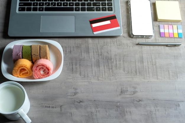 ノートパソコン、スマートフォン、クレジットカード、一杯の牛乳、ジャムロール、ペーパーノート、ペン、ビジネス、商業、金融、教育の概念とデザインの木製テーブルの上から見る