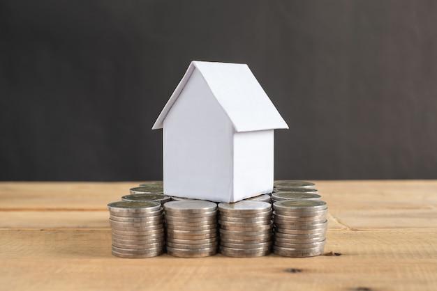 木製のテーブルと黒のコインのスタックのミニ白い家モデルの色。家のお金の概念を保存します。ビジネス、ファイナンス、バンキング、不動産の成長と成長