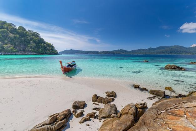 タイの熱帯の島の白い砂浜にロングテールボート