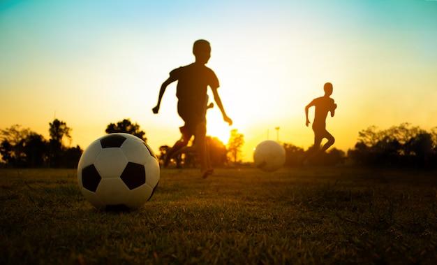 屋外楽しんで子供たちのグループのシルエットアクションスポーツ