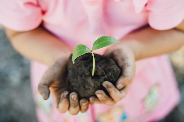 子供は母なる地球日コンセプトの木を植えます。