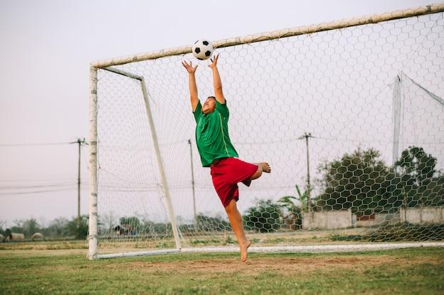 ゴールキーパーとしてサッカーをしている少年のスポーツ写真