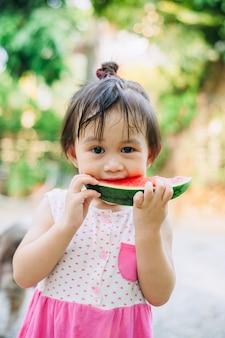 Дети веселятся и отмечают жаркие летние каникулы, поедая арбуз