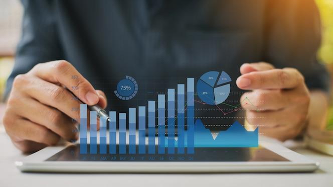 Бизнесмен анализируя баланс финансового отчета компании с цифровыми графиками дополненной реальности.