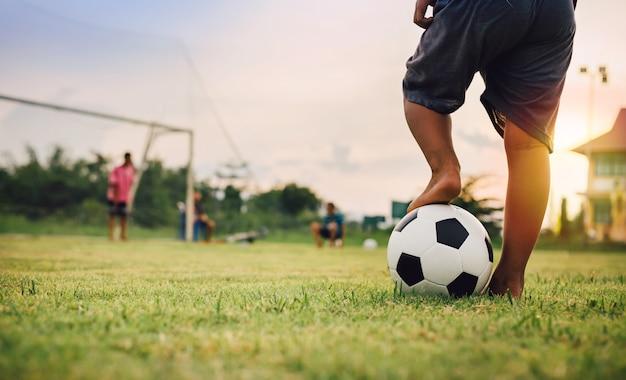 サッカーをして楽しんでいる子供たちのグループの屋外アクションスポーツ