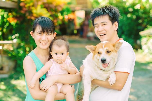 両親と犬との小さな女の赤ちゃん
