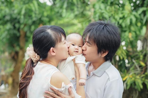 Родители целуют свою маленькую девочку