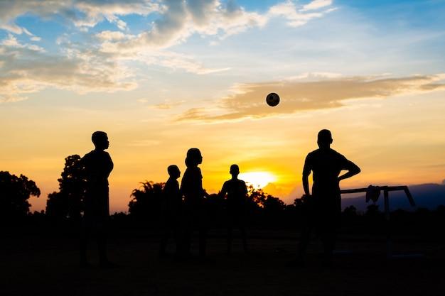 子供たちのグループ(男の子)は、太陽の日の運動のためにサッカーフットボールをしています