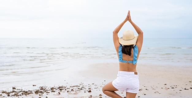 裏側若いアジア女性ヨガビーチ夏のコンセプトの背景に屋外