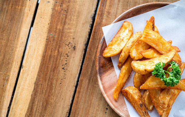 ポテトチップスまたはフライドポテトの木製テーブルトップビュー、食品のコンセプト。