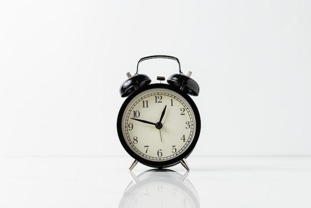 白いテーブルに黒の目覚まし時計。