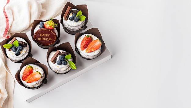 Кекс на белом столе, украшенный клубничной черникой и шоколадной биркой с днем рождения