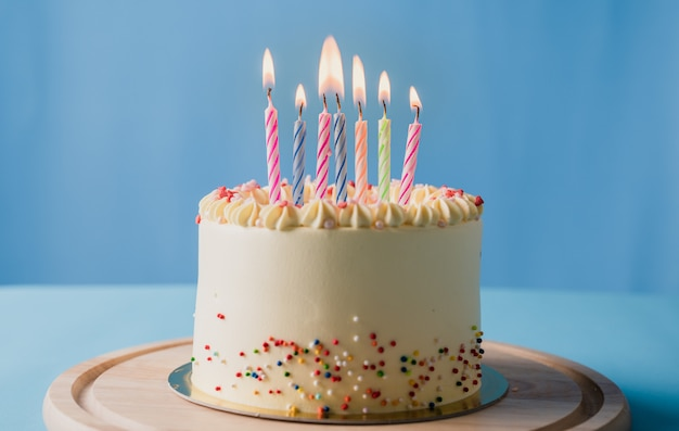 青色の背景にカラフルなキャンドルで誕生日ケーキ