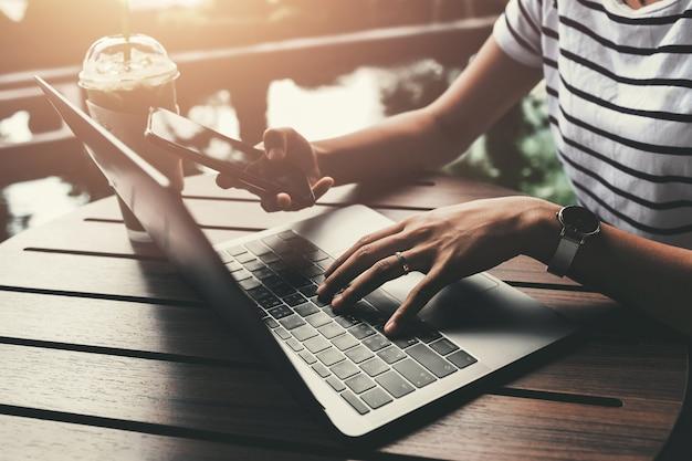 コーヒーショップカフェでオンラインで働くためにモバイルを使用する実業家はラップトップと接続する