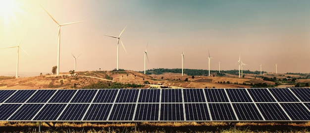 丘と日差しの背景に太陽電池パネルを備えた風力タービン。自然の中の概念クリーンエネルギーの力