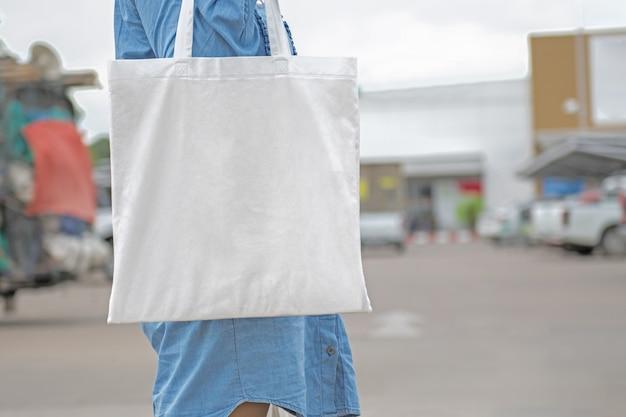 買い物のための綿の袋を保持している女性。エココンセプト