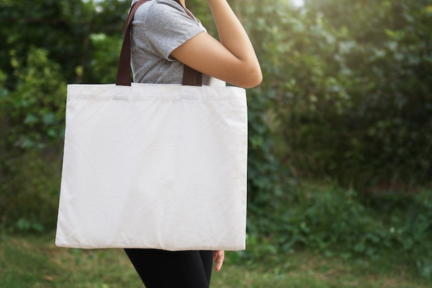 Рука женщины держа сумку хлопка на зеленой предпосылке. эко концепция
